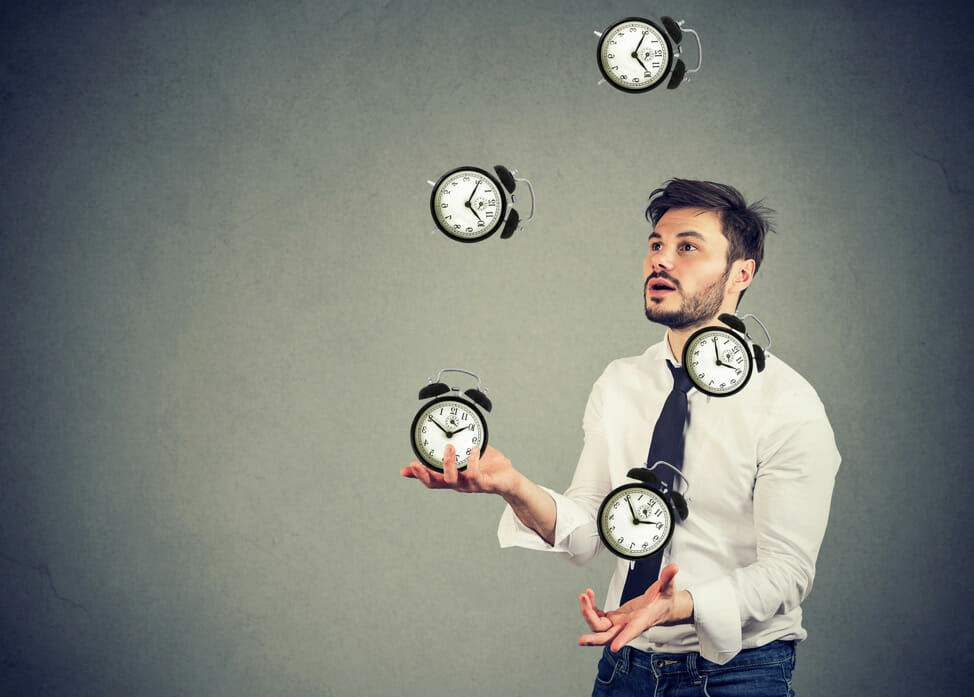 A man juggling five clocks