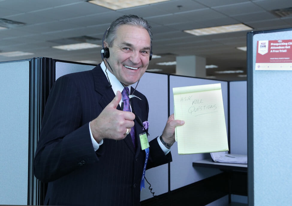 A man smiling as he wears a suit and holds a notepad