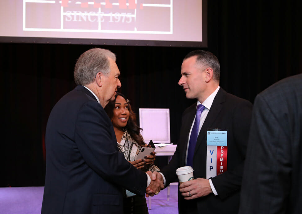 Mike Ferry shaking hands with another Real Estate Agent at an event