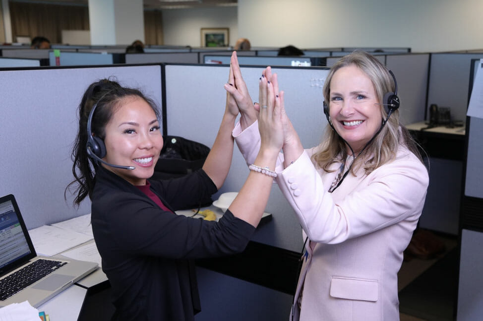 Two women Real Estate Agents smiling while wearing headsets