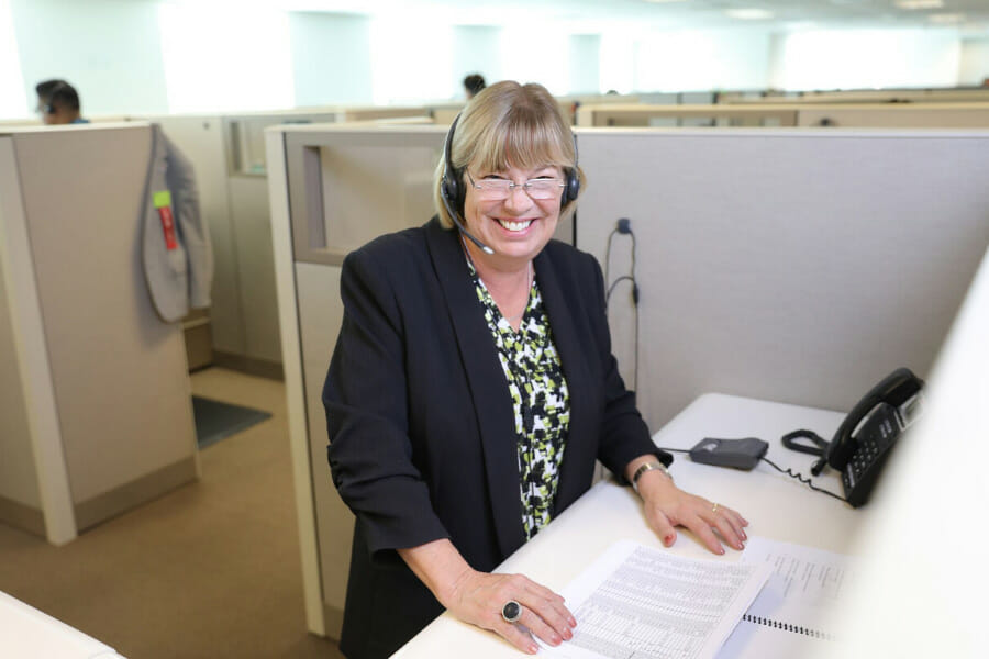 A woman with glasses smiling at her desk